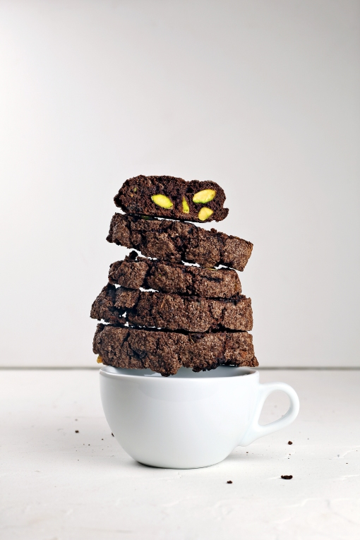 Double chocolate & pistachio biscotti perched on a coffee cup